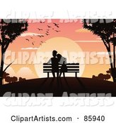 Silhouetted Couple Sitting in a Bench and Watching the Sun Set
